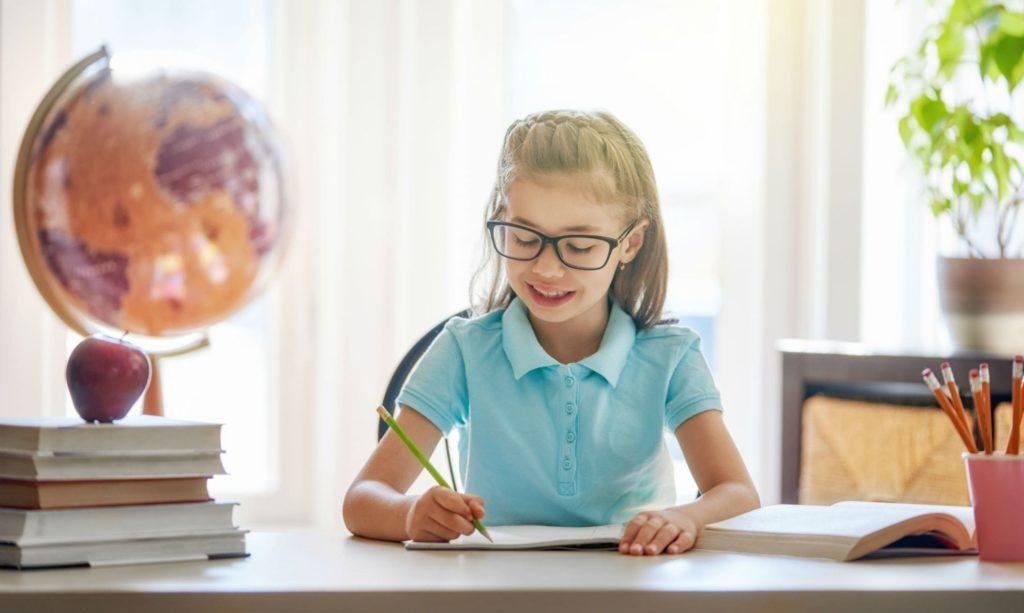 child is sitting at a desk indoors AU7ZJGQ min